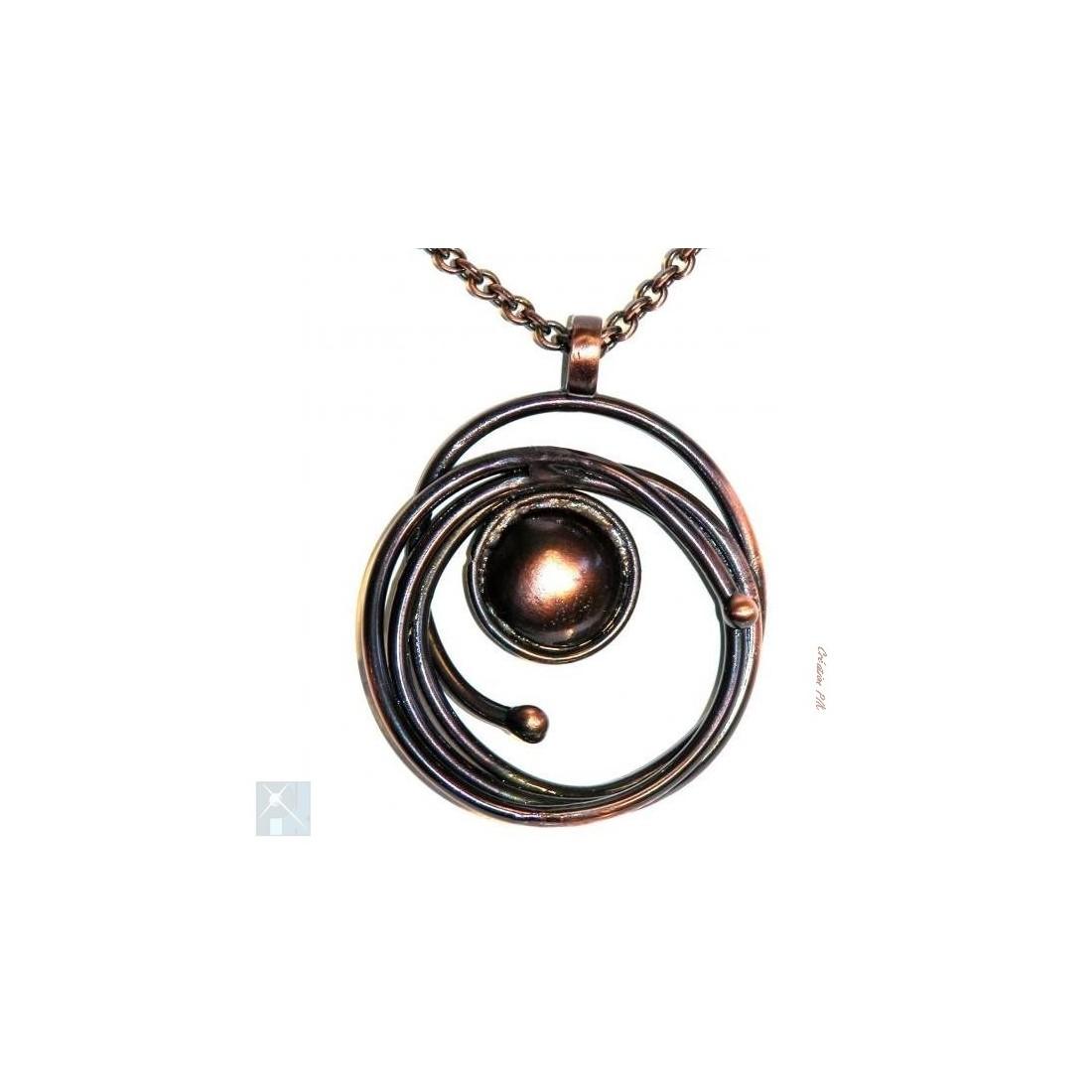 Pendentif artisanal de couleur cuivrée sur une chaîne longue
