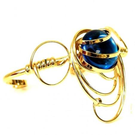 Bracelet doré avec une pierre bleu saphir.