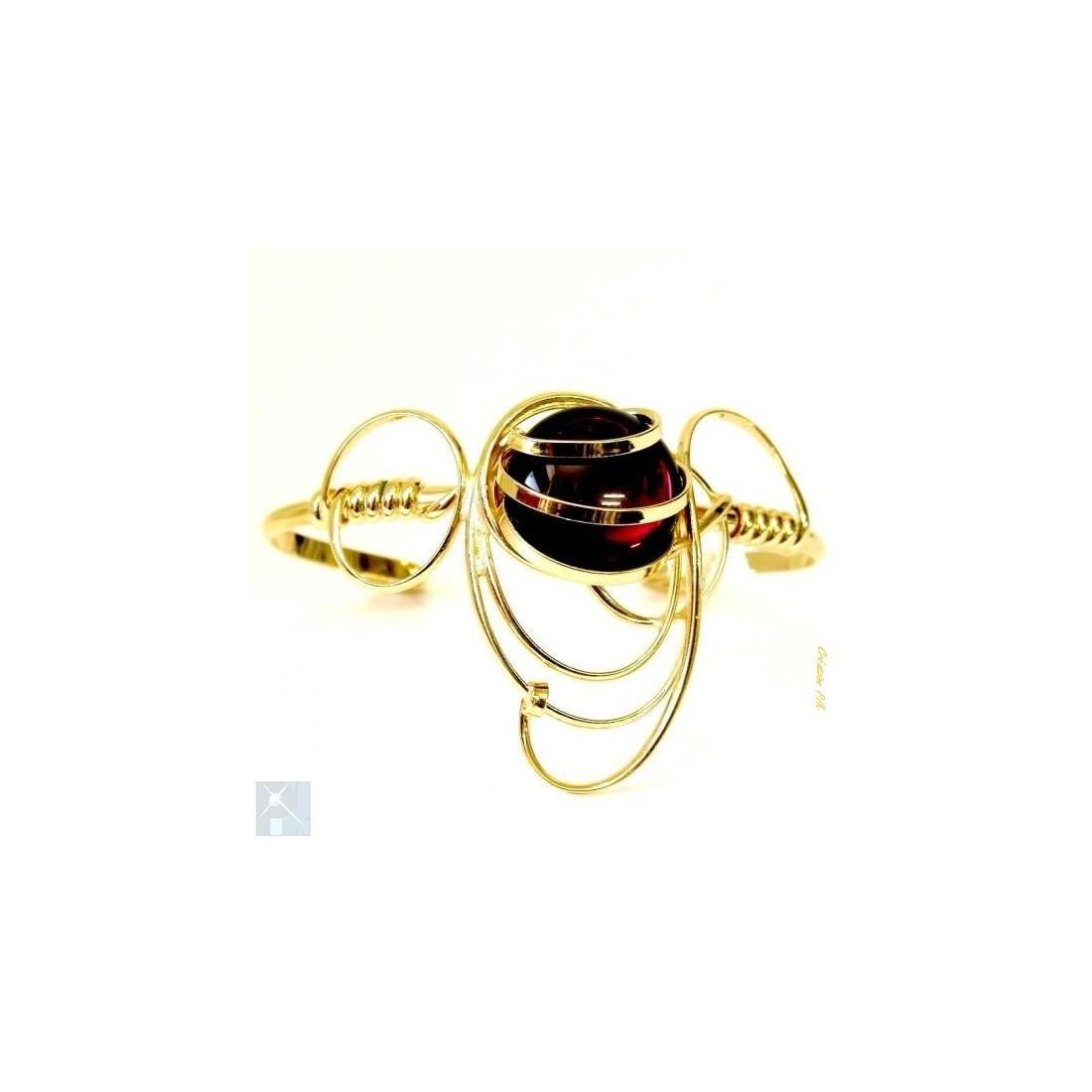 Bracelet doré de créateur avec une pierre de couleur améthyste.