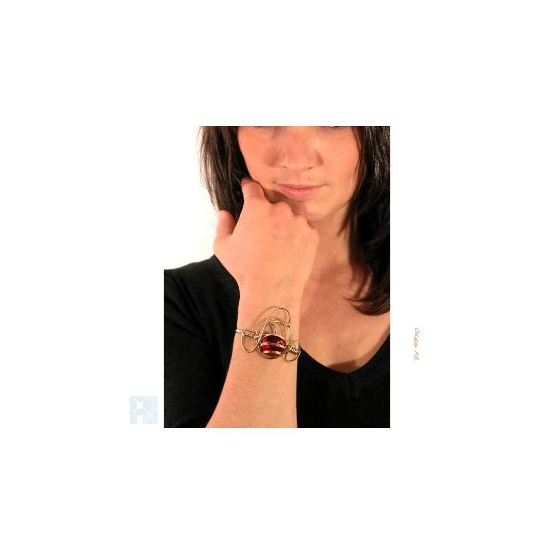 Bracelet de créateur de couleur or avec une  pierre rouge.