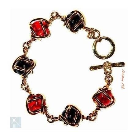Bracelet souple doré avec six strass rouges et noirs. Bijou fait main.