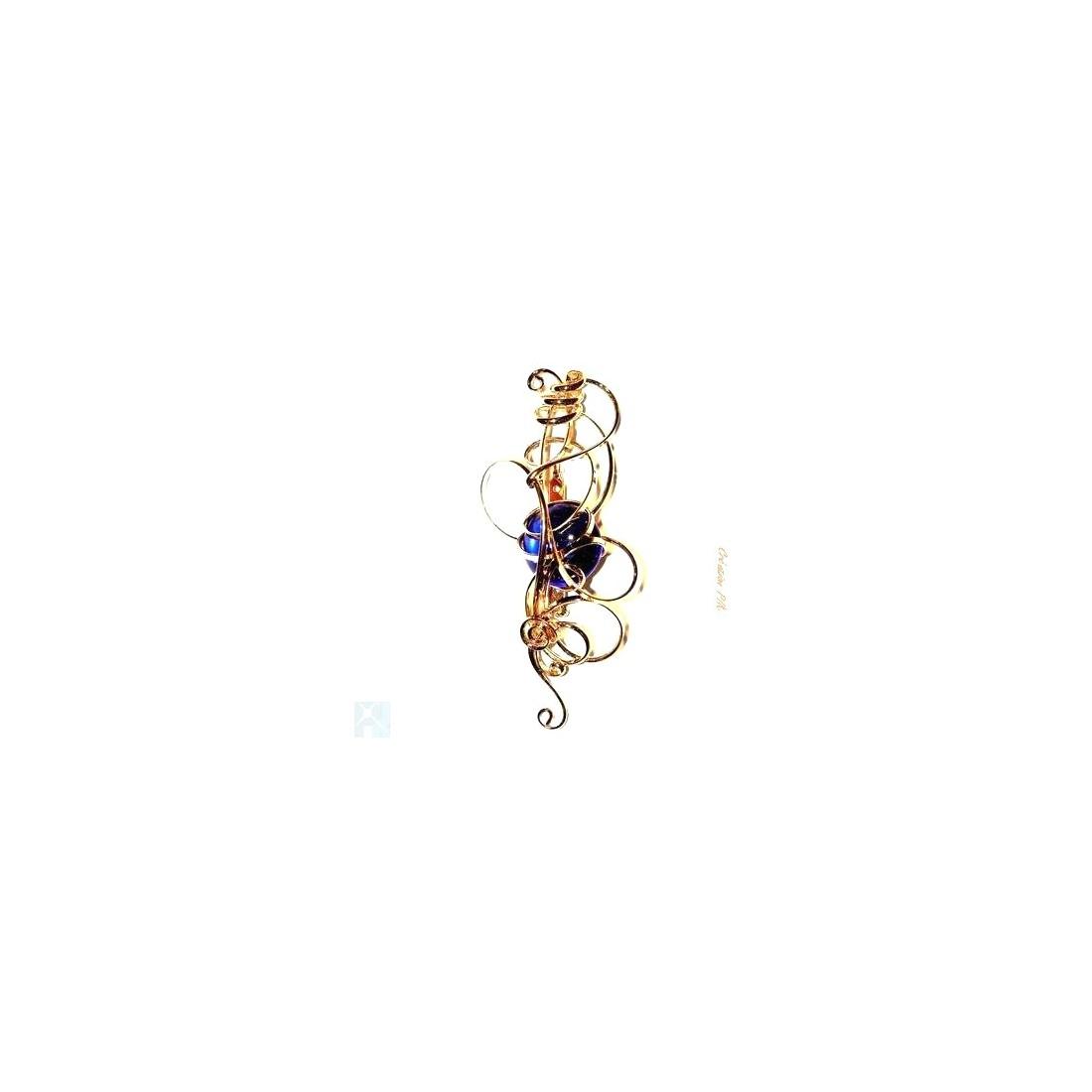 Broche fantaisie dorée avec une pierre bleue foncée